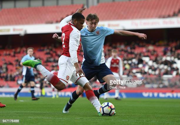 Vontae DaleyCampbell of Arsenal crosses the ball under pressure from Nathan Shaw of Blackpool during the match between Arsenal and Blackpool at...