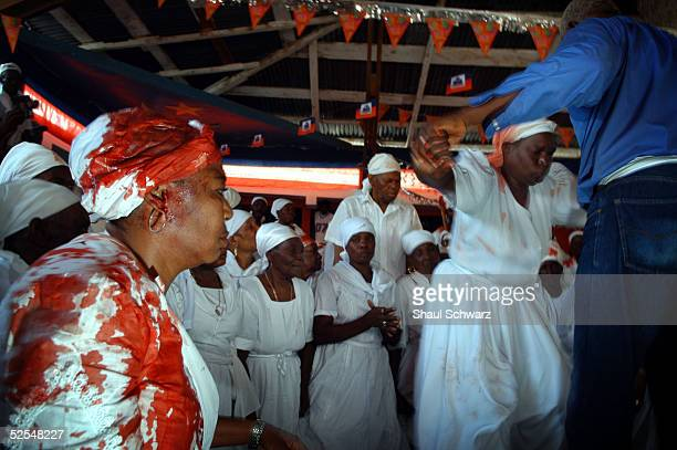 Voodoo believers dance with blood on their white cloth after sacrificing goats during a ritual at the Voodoo temple compound March 27 2005 at...