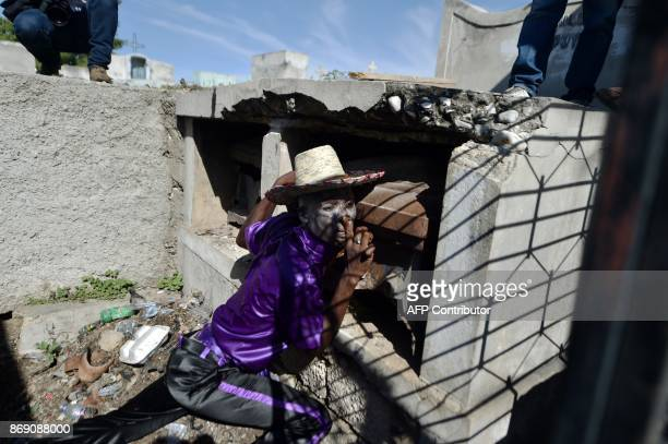 A voodoo devotee in the role of a spirit known as a Gede is leaning on a coffin during ceremonies honoring the Haitian voodoo spirit of Baron Samdi...