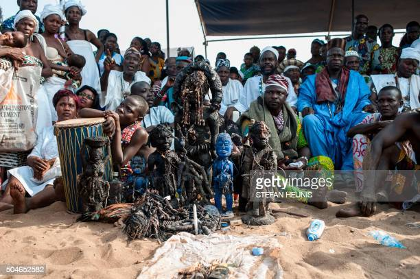 TOPSHOT Voodoo devotees sit around voodoo idols made of bronze wood rope hair and feathers on a beach in Ouidah on January 10 2016 Officially...