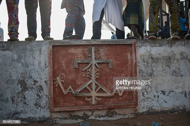 Voodoo devotees stand on a low wall with a voodoo sign inscription at the beach in Ouidah on January 10 2016 Officially declared a religion in Benin...