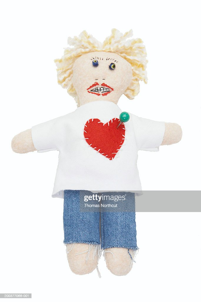 Voodoo doll with straight pin in heart : Stock Photo