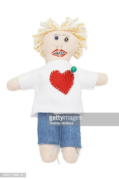 voodoo doll with straight pin in heart - voodoo doll stock photos and pictures
