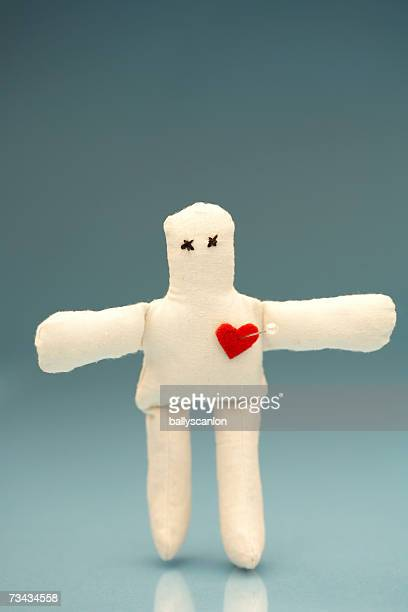 Voodoo doll with straight pin in heart