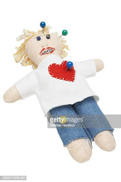 Voodoo doll with straight pins in leg, heart and head, elevated view