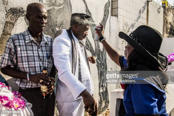 Voodoo faithful celebrate Baron Samedi during a ceremony commemorating the Day of the Dead at the National Cemetery in PortauPrince on November 1 2019