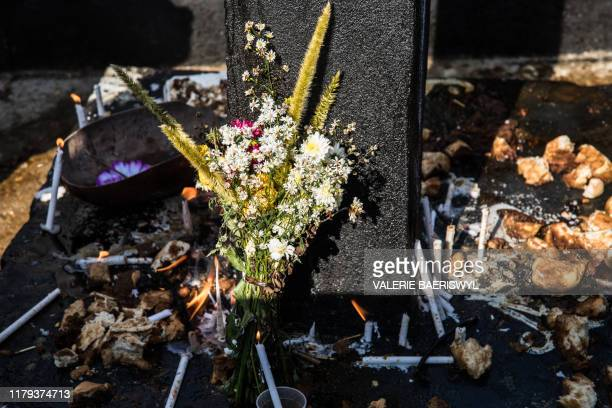 Voodoo faithful leave flowers and food to celebrate Baron Samedi during a ceremony commemorating the Day of the Dead at the National Cemetery in...