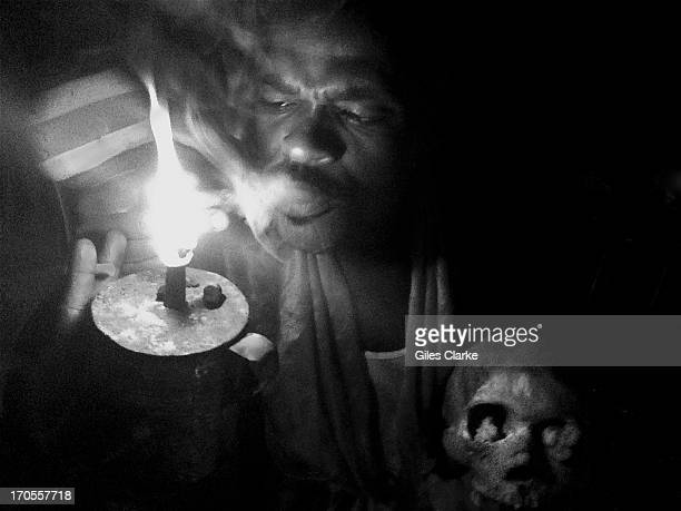 Voodoo High Priest 'Joumabon' lights a pipe of tobacco in his altar room March 22 2013 in Jacmel Haiti The ceremony takes places in a simple outhouse...