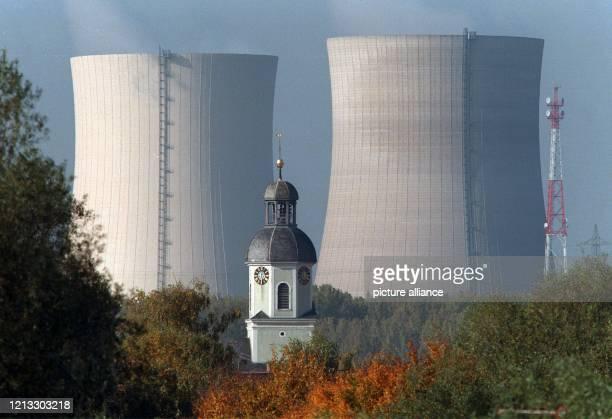 Vor den Kühltürmen des Kernkraftwerks Philippsburg ragt der Kirchturm der Gemeinde Philippsburg hervor Die zwei Blöcke des KKWs decken rund ein...