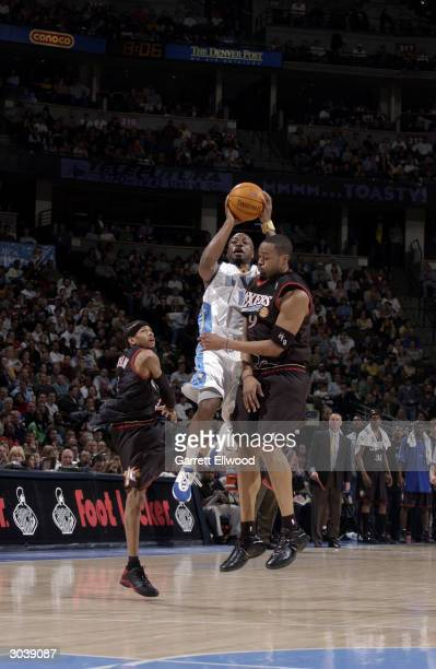 Voshon Lenard of the Denver Nuggets shoots over Eric Snow and Allen Iverson of the Philadelphia 76ers during the game at the Pepsi Center on February...