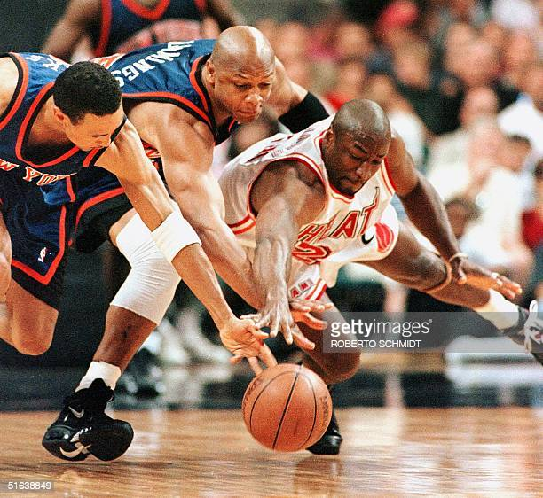 Voshon Lenard of the Miami Heat and Terry Cummings and John Starks of the New York Knicks lunge for a loose ball in the first quarter of the fifth...