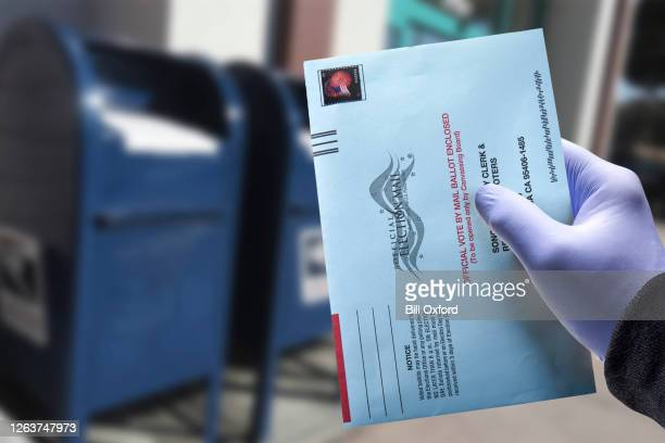 vote by mail with glove: person mailing absentee ballot wearing a protective surgical glove for voting - voting by mail stock pictures, royalty-free photos & images