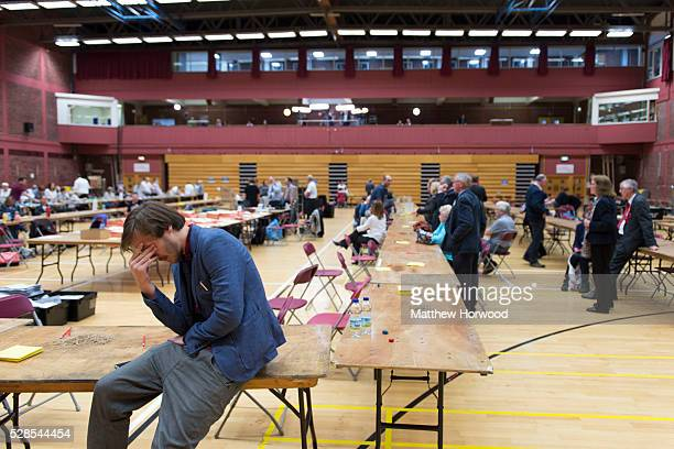 A vote counter sits with his head in his hand as counting continues into the morning during the National Assembly for Wales election count at the...