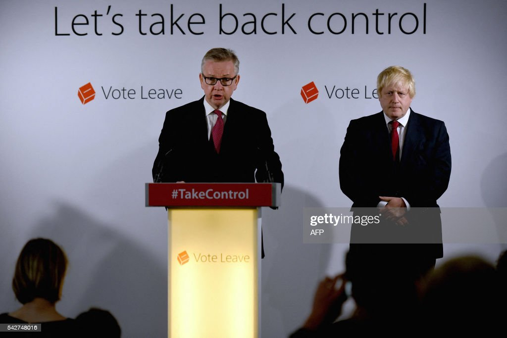 Vote Leave campaigners, British Lord Chancellor and Justice Secretary Michael Gove (C) speaks as former London Mayor Boris Johnson listens during a press conference at the Vote Leave headquarters in central London on June 24, 2016 after the UK voted to leave the European Union. Boris Johnson, who spearheaded the successful campaign for Britain to leave the European Union, said Friday there was no need to rush the process of pulling out of the bloc. / AFP / POOL / Mary Turner