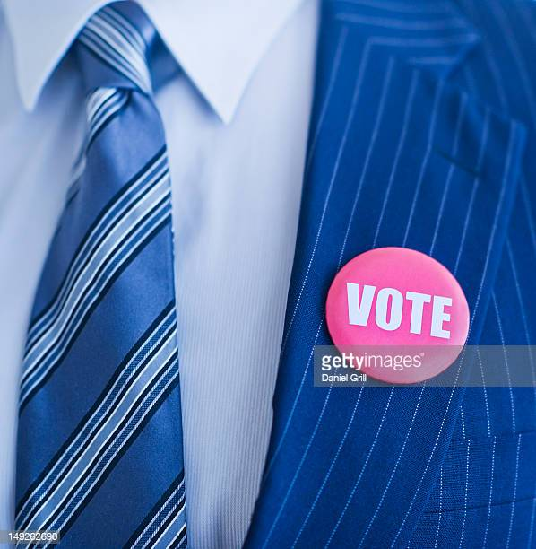 vote pin on man's lapel - campaign button stock pictures, royalty-free photos & images
