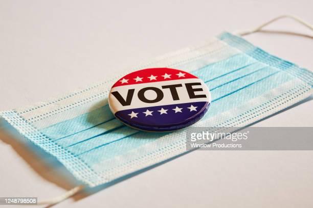 vote pin on surgical mask - election imagens e fotografias de stock