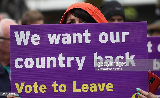Vote to Leave campaigner holds a placard as Leader of the United Kingdom Independence Party Nigel Farage campaigns for votes to leave the European...