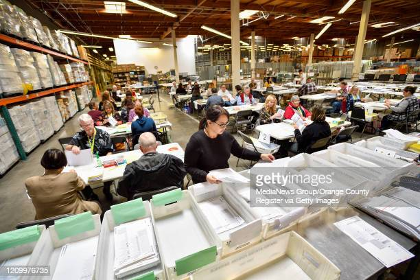 "Vote-by-mail processors work to check mail-in ballots the day before election day at the Orange County Registrar""u2019s office in Santa Ana, CA, on..."