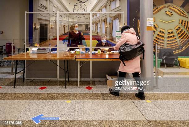 Voter arrives to cast a vote in the 2021 Dutch general elections at the House of Representatives in the Hague on March 17, 2021. - Polling stations...