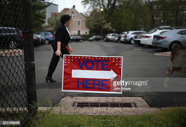 A voter arrives to cast her ballot at a polling center located in a high school gymnasium on April 26 2016 in Stamford Connecticut Democratic and...