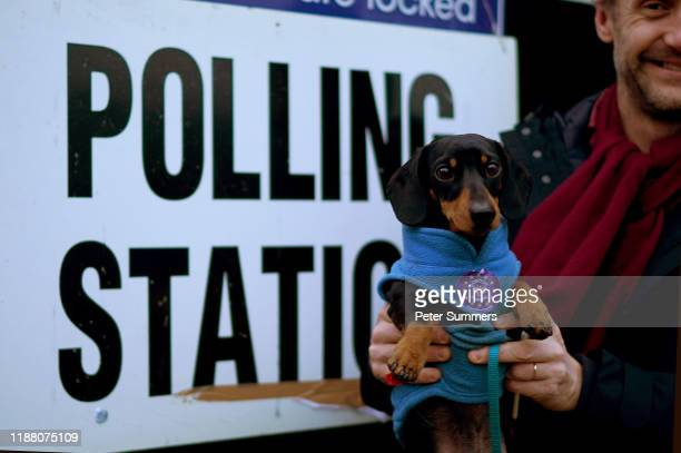 A voter carries his dog with a proEU sticker on its coat at the polling station at Pakeman Primary School Holloway on December 12 2019 in London...