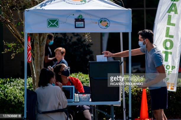 Voter cast his ballot at a vote by mail ballot box at the Alafaya Branch Library in Orlando, Florida, on October 30, 2020. - Trump and Biden are...