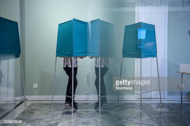 A voter casting a ballot is reflected in a mirror at a polling station during the Swedish general elections in Stockholm Sweden in Sunday Sept 9 2018...