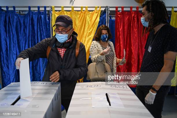 Voter casts a ballot at a polling station in Bucharest on September 27, 2020. - Amid a surge of COVID 19 cases, Romanians are called to elect local...