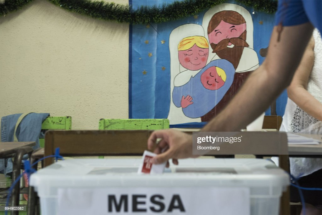 A voter casts a ballot during the second-round presidential general elections in Santiago, Chile, on Sunday, Dec. 17, 2017. Billionaire Sebastian Pinera swept to victory in the second round of Chiles presidential election, putting him back in charge of Latin Americas wealthiest country after four years of anemic growth that drew millions of voters to his pro-business agenda. Photographer: Tamara Merino/ Bloomberg