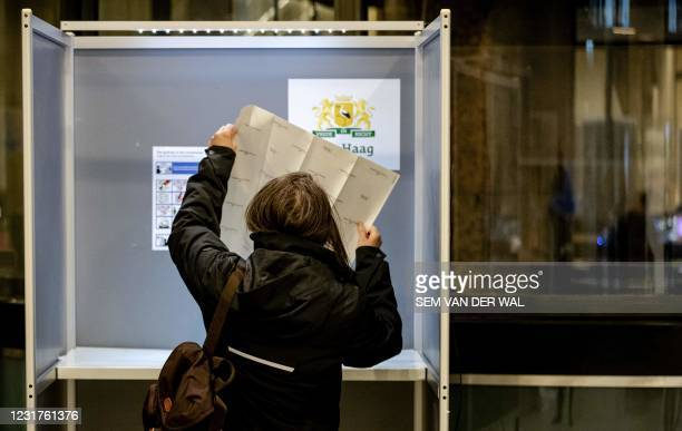 Voter casts a vote in the 2021 Dutch general elections at the House of Representatives in the Hague on March 17, 2021. - Polling stations opened on...