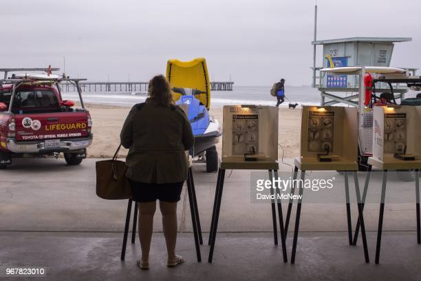 A voter casts her ballot at a Los Angeles County lifeguard headquarters at Venice Beach on June 5 2018 in Los Angeles California California could...