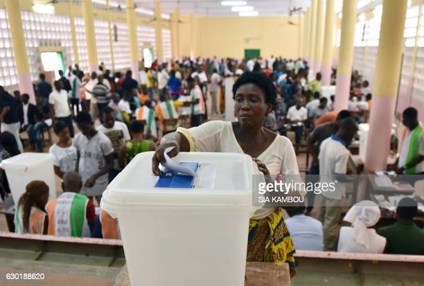 A voter casts her ballot into an urn at a polling station in Le Plateau the central business district of Abidjan on December 18 during legislative...