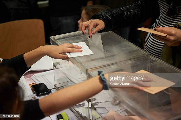 A voter casts her ballot paper for the Spanish general election into the ballot box at a polling station on December 20 2015 in Madrid Spain...