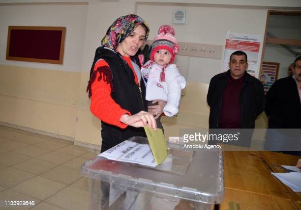 A voter casts her ballot with her baby at a polling station during local elections in Mus Turkey on March 31 2019 Polling in Turkeys local elections...