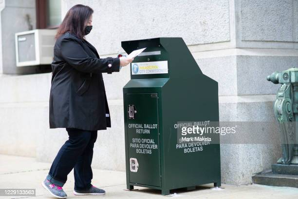 Voter casts her early voting ballot at drop box outside of City Hall on October 17, 2020 in Philadelphia, Pennsylvania. With the election only a...