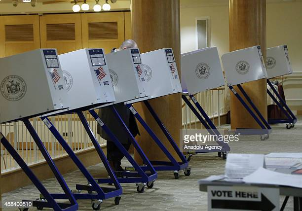 A voter casts his ballot at a polling station during the US midterm elections in New York United States on November 4 2014 US voters were headed to...