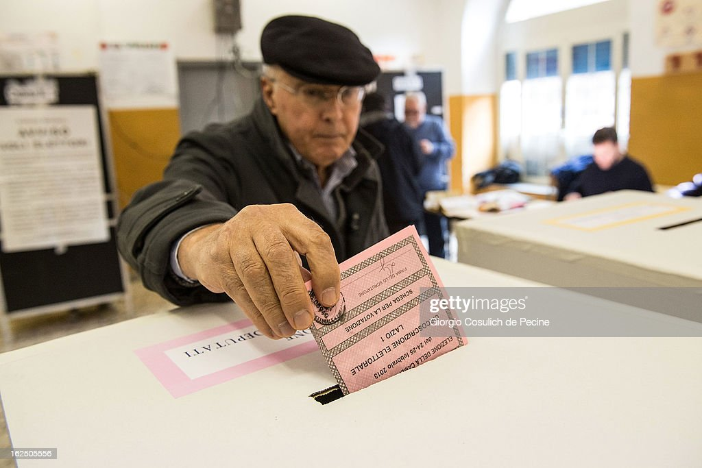 A voter casts his ballot at a polling station on February 24, 2013 in Rome, Italy. Italians are heading to the polls today to vote in the elections, as the country remains in the grip of economic problems . Pier Luigi Bersani's centre-left alliance is believed to be a few points ahead of the centre-right bloc led by ex-Prime Minister Silvio Berlusconi.