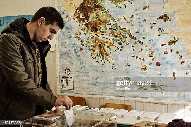 A voter casts his ballot in front of a map of Greece at a polling station in a school on January 25 2015 in Athens Greece According to the latest...