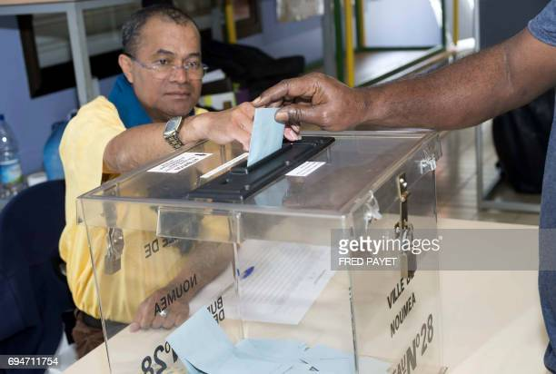 A voter casts his ballot in the first round of the French legislative elections at a polling station in Noumea in the French overseas territory of...
