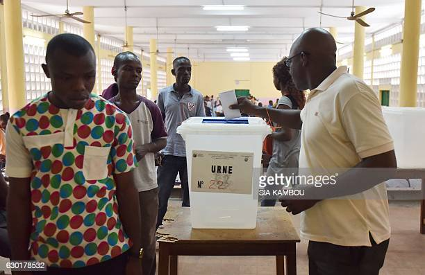 A voter casts his ballot into an urn at a polling station in Le Plateau the central business district of Abidjan on December 18 during legislative...