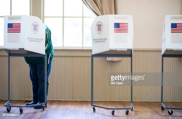 A voter casts his vote at the Hillsboro Old Stone School in Virginia's 10th Congressional district Rep Barbara Comstock's district on primary...