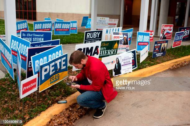 A voter checks his phone before casting his ballot during the presidential primary in Houston Texas on Super Tuesday March 3 2020 Fourteen states and...