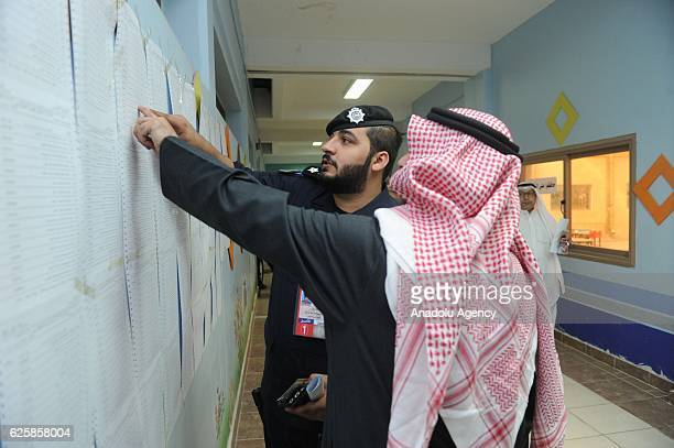 A voter checks the voters list before casting his ballot during the general election at the Sayyed Hassan AlMusawi school on November 26 in Kuwaiti...