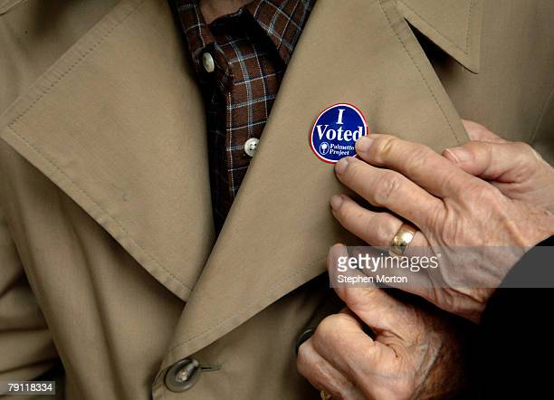 Voter Claire Young places a 'I Voted' sticker on her husband John Young's lapel after he cast his ballot at during the South Carolina Republican...