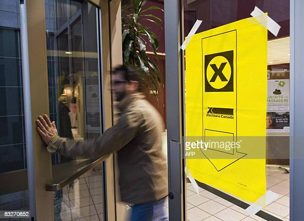 A voter comes from a polling center after casting his ballot October 14 2008 in St Laurent Quebec Canada Canadians voted in their third election in...