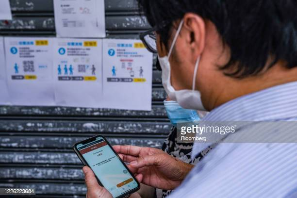 A voter confirms registration using a smartphone while standing in line outside a temporary polling station set up by a yellow economy restaurant...