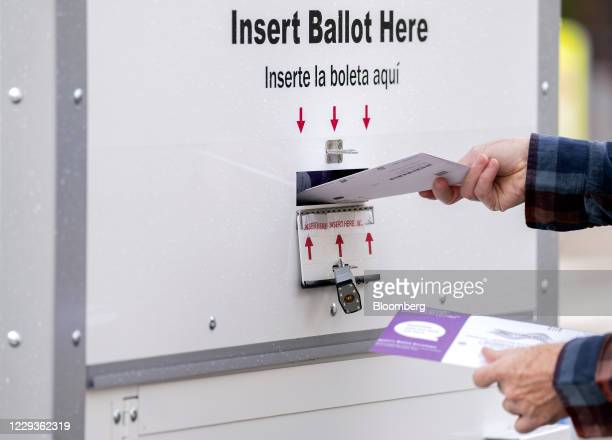 Voter deposits a ballot into an Official Ballot Drop Box in Washington, D.C., U.S., on Friday, Oct. 30, 2020. Early voting in the Presidential...
