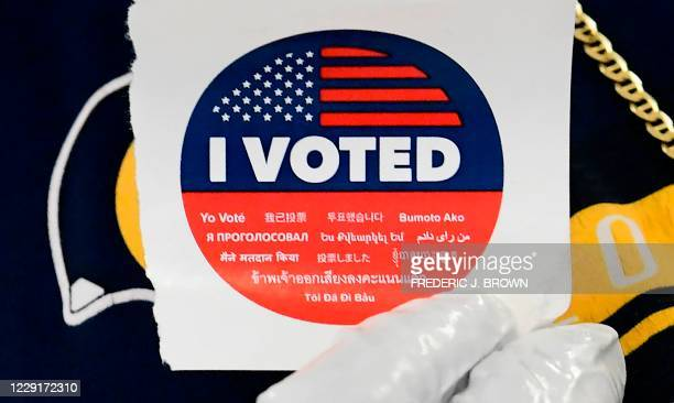 "Voter displays his ""I Voted"" sticker, with the words ""I Voted"" in multiple languages, after casting his vote in the 2020 US elections at the Los..."
