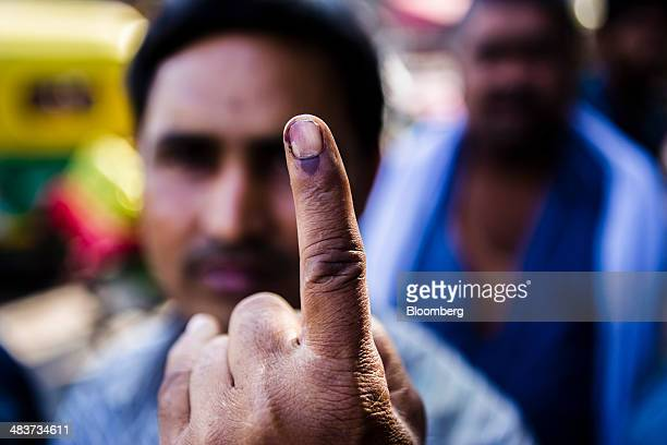 A voter displays his inked finger for a photograph after casting his vote at a polling station during the third phase of voting for national...