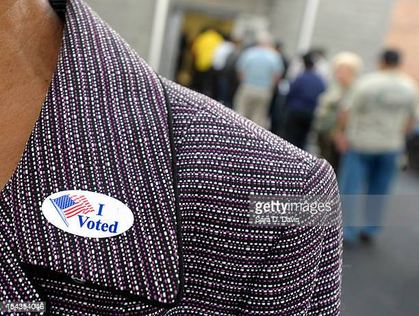 A voter displays their I Voted sticker on their lapel after voting as others wait in line for the first day of Early Voting on October 18 2012 in...